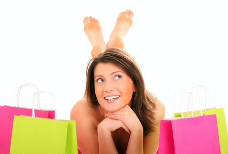 A picture of a pretty young woman lying among shopping bags over white background photo