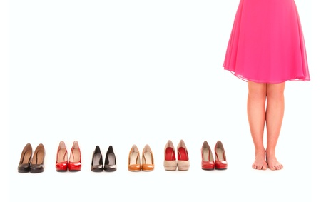 A picture of sexy female legs among six pairs of shoes over white background photo