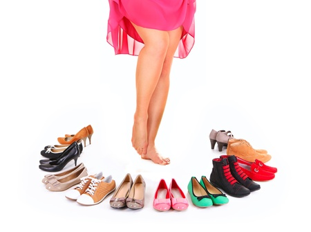 A picture of a pretty young woman sitting in the circle of shoes over white background Stock Photo - 12612370