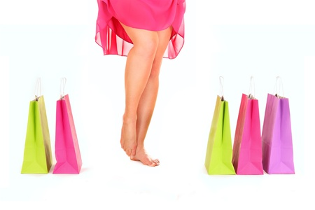 A picture of sexy female legs among shopping bags over white background photo