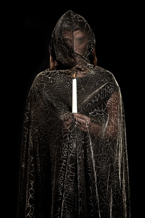 black magic: A picture of a mysterious person standing against dark background with a candle