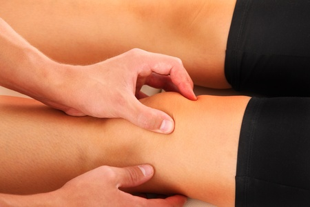 A picture of a physio therapist giving a knee massage  photo