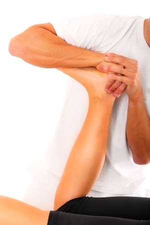 sportmassage: Een foto van een fysio therapeut probeert het been op een witte achtergrond te lossen