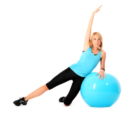 A picture of a beautiful young fit woman sitting on a ball and stretching over white background photo