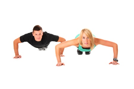 A picture of a young couple doing push-ups over white background photo