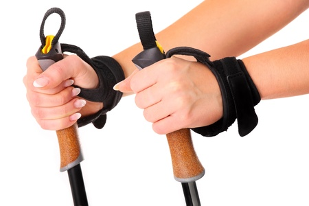 walking stick: A close-up of female hands holding nordic walking sticks over white background Stock Photo