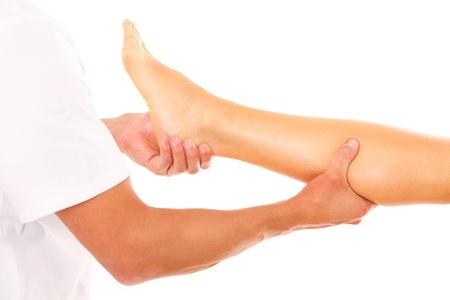 masaje deportivo: Una foto de un fisioterapeuta dando un masaje en las piernas sobre el fondo blanco Foto de archivo
