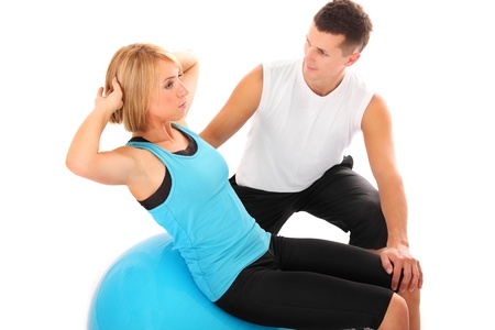 'personal beauty': A picture of a young woman working out with her personal trainer over white background