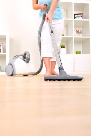 bright housekeeping: A picture of a young wife hoovering her apartment