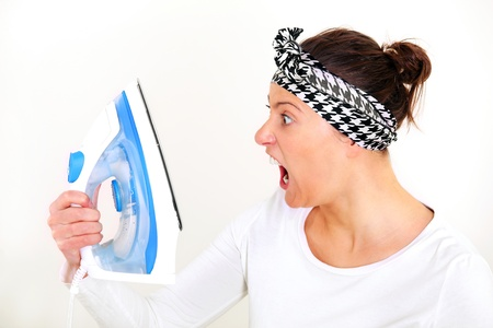 woman ironing: A picture of a tired unhappy housewife shouting at her iron over white background Stock Photo
