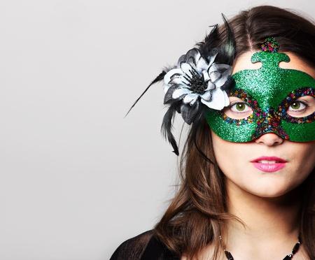 Una imagen de una mujer joven que llevaba una máscara de carnaval sobre fondo gris Foto de archivo