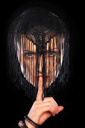 burqa: A picture of a young muslim girl with her finger on lips showing to keep quiet