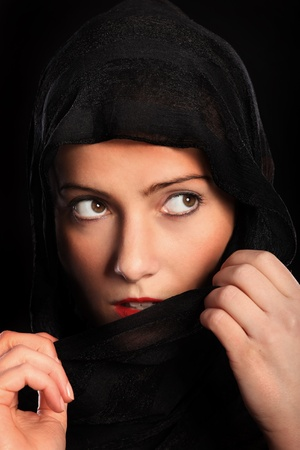 fear face: A picture of a young muslim girl over black background Stock Photo
