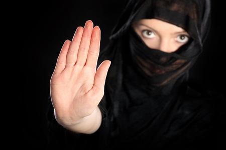 burka: Un ritratto di una giovane donna araba che mostra di fermare su sfondo nero
