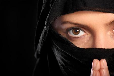 burka: Un ritratto di una giovane donna arabo concentrato sulla sua preghiera, su sfondo nero Archivio Fotografico