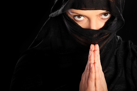 burqa: A picture of a young arabic woman focused on her prayer over black background Stock Photo