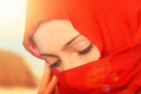 headscarf: A portrait of a sad arabic woman standing in the sun Stock Photo