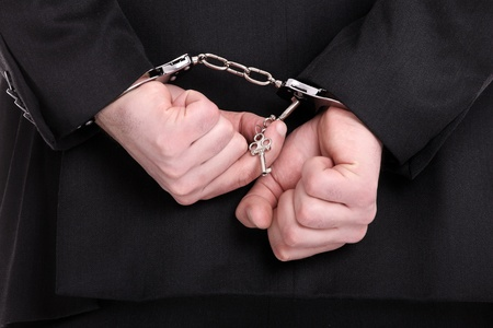 A picture of a businessman trying to unlock his handcuffs photo