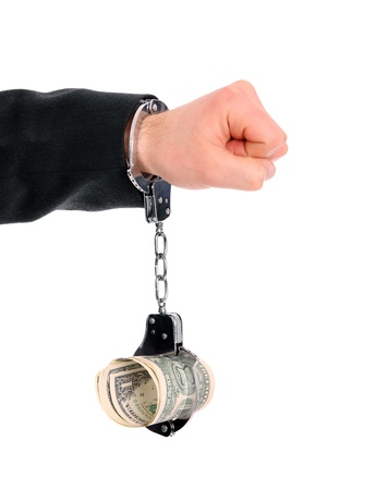 A picture of a male hand chained to money over white background photo