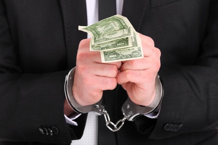 venality: A picture of a businessman in handcuffs holding dollars