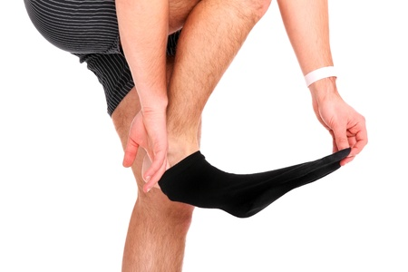 A picture of a man taking off his socks over white background Imagens