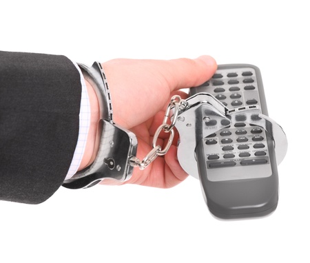venality: A picture of a male hand chained to remote control over white background