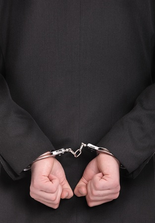 A picture of a businessman in handcuffs standing over white background photo