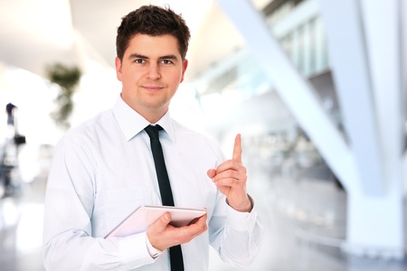 A portrait of a young businessman standing over the background of his modern office photo