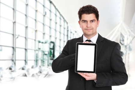 A portrait of a young businessman standing over the background of his modern office and presenting your product on tablets screen photo