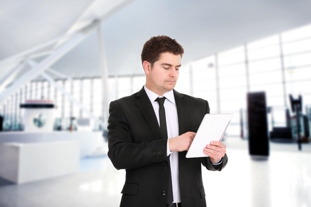 A portrait of a young businessman standing over the background of his modern office and using tablet computer photo