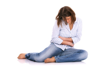 aches: A picture of a young woman sitting on the floor and suffering from stomach ache