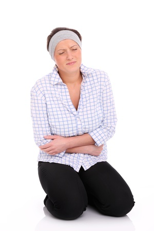A picture of a young woman sitting on the floor and suffering from stomach ache Stock Photo - 13069221