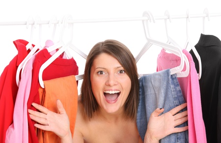 A picture of a young happy girl surrounded by clothes over white background photo