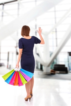 A picture of a young woman with shopping bags waving goodbye Stock Photo - 13325136