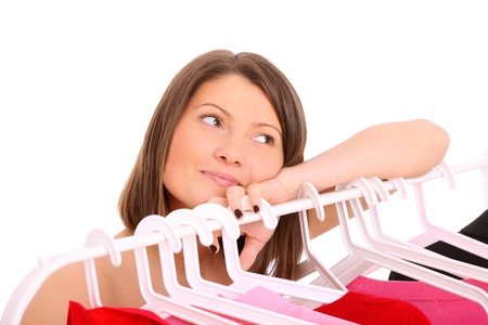 decission: A picture of a young happy girl surrounded by clothes over white background