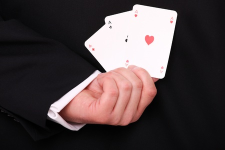 A picture of a young businessman hand holding three aces behind the back photo