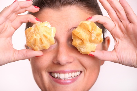 A close up of a young woman covering her eyes with cream puffs over white background photo