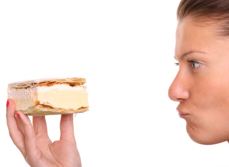 A close up of a young woman trying to resist temption of eating a cream puff over white background photo