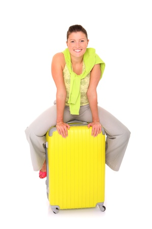 A picture of a young woman sitting on a big suitcase over white background Stock Photo - 13877463