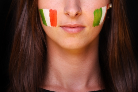 A picture of a young woman with Italian flags on cheeks standing over black background Stock Photo - 13877473