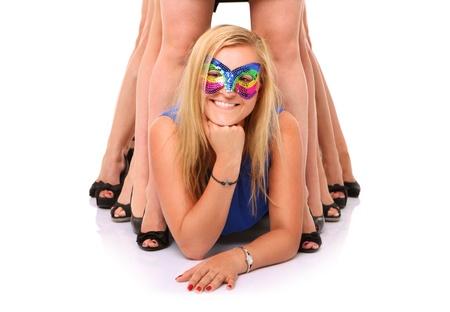 despedida de soltera: Un retrato de una hermosa chica rubia que se extiende entre las piernas de sus novias sobre fondo blanco
