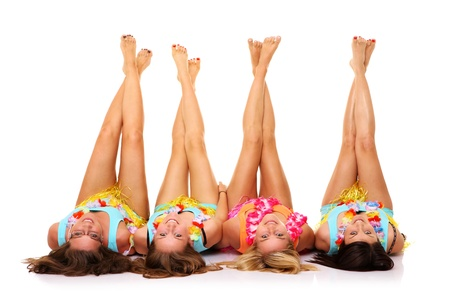 A picture of four girlfriends lying on the floor in hawaiian skirts with their legs up over white background