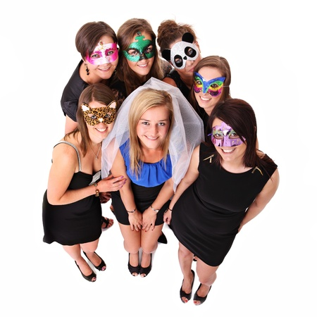 A portrait of seven girlfriends in carnival masks smiling over white background photo