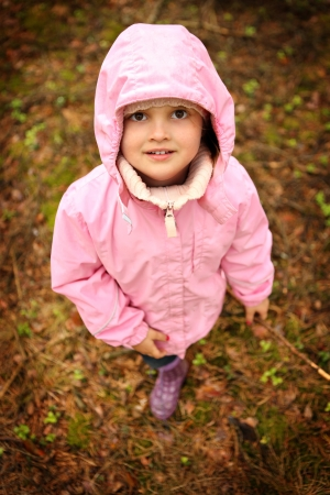 welly: A picture of a little girl in pink outfit walking in the forest