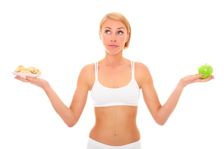 A picture of a young fit woman deciding between eating an apple or cookies over white background photo