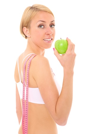 A picture of a young fit woman with a green apple and a tape measure over white background photo