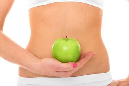 'flat stomach': A picture of a woman holding a green apple in front of her fit belly