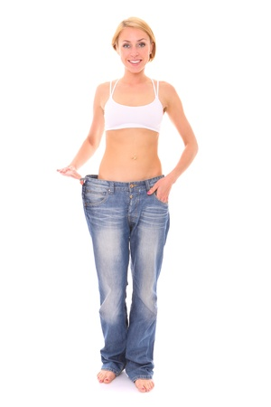 A picture of a young fit woman showing too big jeans as diet effects over white background Stock Photo - 14248784