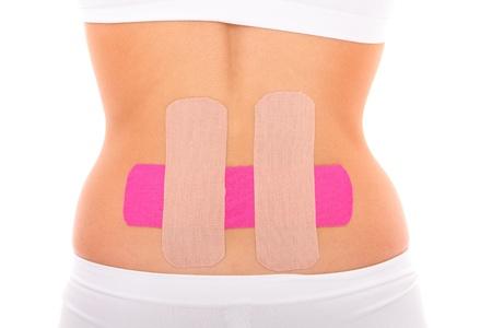 fisioterapia: Una foto de un especial de la cinta fisio poner en el músculo de la espalda sobre el fondo blanco Foto de archivo