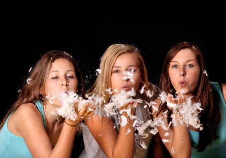 A picture of three friends blowing feather over black backgrund Stock Photo - 14394390